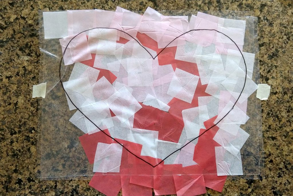 A simple, easy and inexpensive kids craft, these contact paper heart suncatchers are a fun way to let the kids help decorate for Valentine's Day.