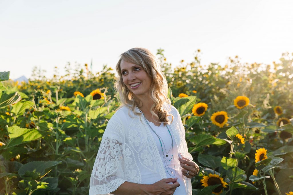 Maternity photo shoot inspiration in a field of sunflowers at sunset.